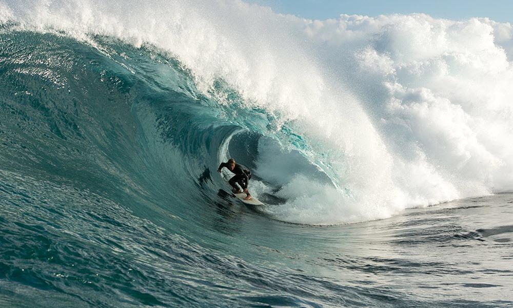 surfer riding barrel wave in margaret river