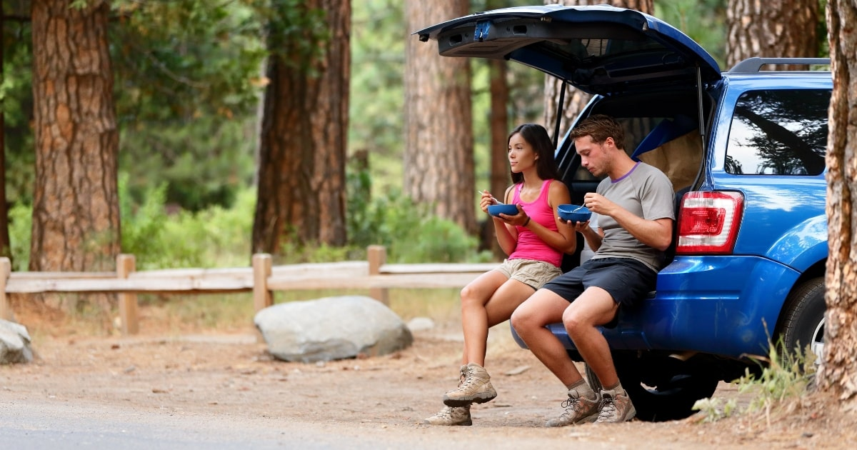 Man and woman sitting on back of car with road trip essential items.