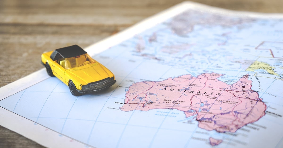 Road trip map of Australia with small yellow toy car.