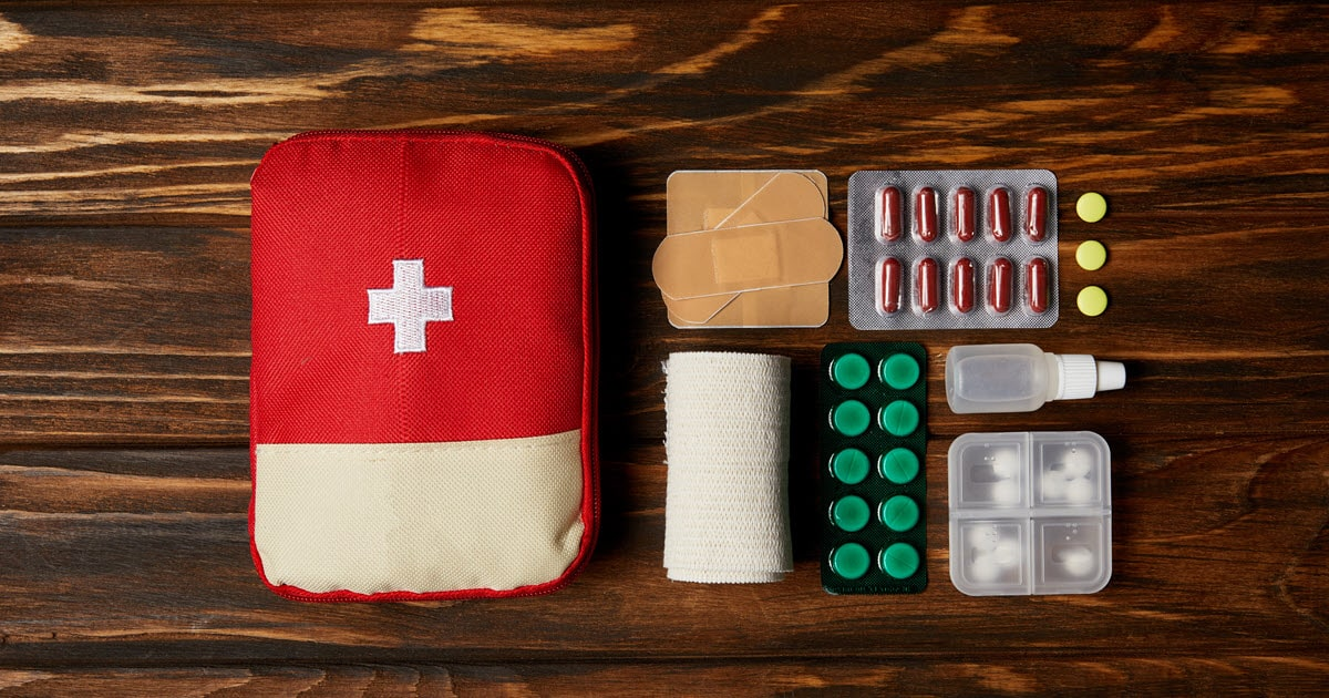First aid kit essentials for road trip on wooden bench.